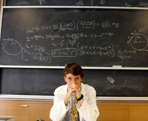 boy with complex formula written on board behind him